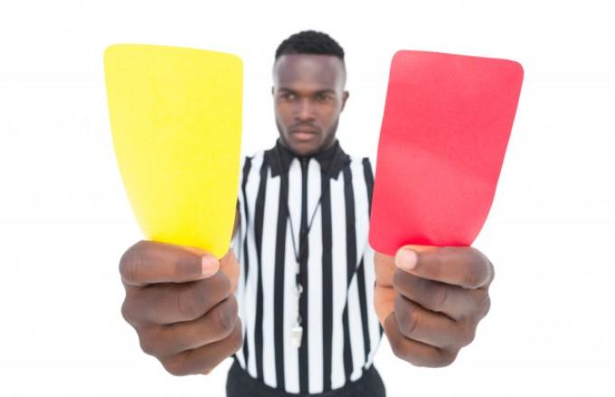 Schiedsrichter zeigt gelbe und rote Karte
